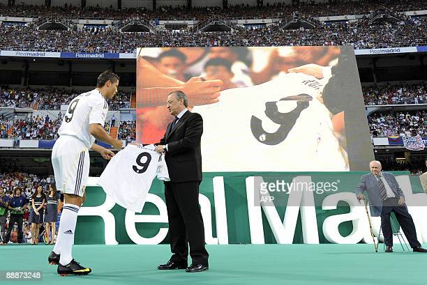 Real Madrid's new player Portuguese Cristiano Ronaldo gives his signed new number 9 jersey next to Real Madrid president Florentino Perez next to...