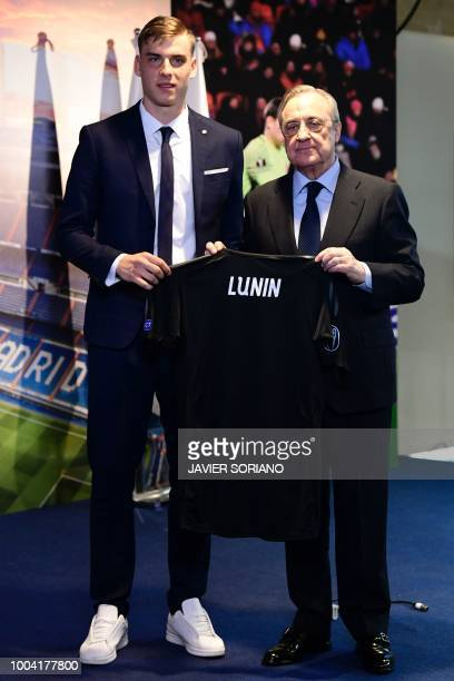 Real Madrid's new Ukrainian goalkeeper Andriy Lunin holds his new jersey as he poses with Real Madrid president Florentino Perez during his official...