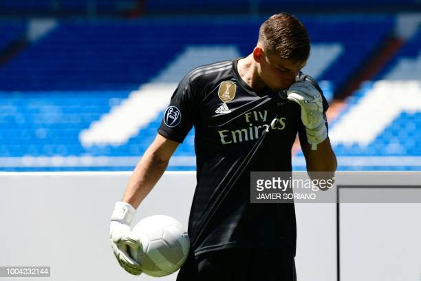 Real Madrid's new Ukrainian goalkeeper Andriy Lunin kisses his new jersey as he poses on the pitch during his official presentation at the Santiago...