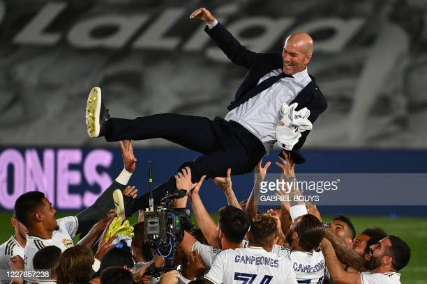 Real Madrid's player toss Real Madrid's French coach Zinedine Zidane after winning the Liga title after the Spanish League football match between...