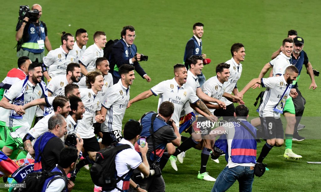 TOPSHOT - Real Madrid's players celebrate winning the Liga title after the Spanish league football match Malaga CF vs Real Madrid CF at La Rosaleda stadium in Malaga on May 21, 2017. /