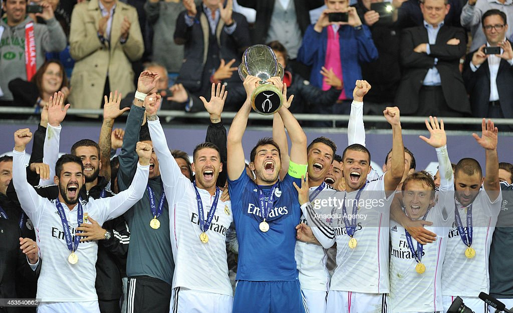 Real Madrid's players celebrate with the trophy after winning the UEFA Super Cup football match between Real Madrid and FC Sevilla on August 12, 2014 at Cardiff City Stadium in Cardiff, Wales on August 12, 2014.
