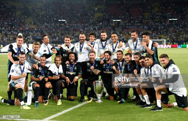Real Madrid's players celebrate with the trophy after winning the UEFA Super Cup football match between Real Madrid and Manchester United on August 8...