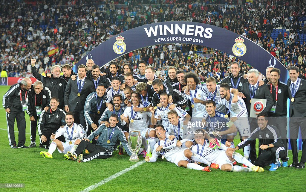 Real Madrid's players pose as they celebrate after winning the UEFA Super Cup football match between Real Madrid and FC Sevilla on August 12, 2014 at Cardiff City Stadium in Cardiff, Wales on August 12, 2014.