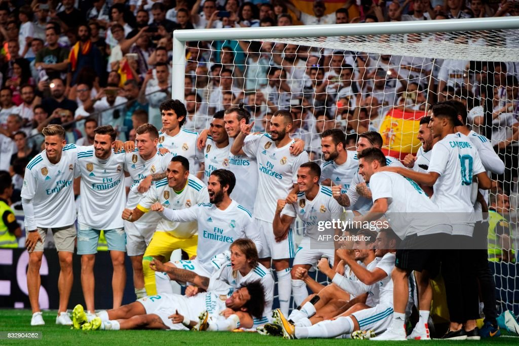 Real Madrid's players pose as they celebrate their Supercup after winning the second leg of the Spanish Supercup football match Real Madrid vs FC Barcelona at the Santiago Bernabeu stadium in Madrid, on August 16, 2017. /