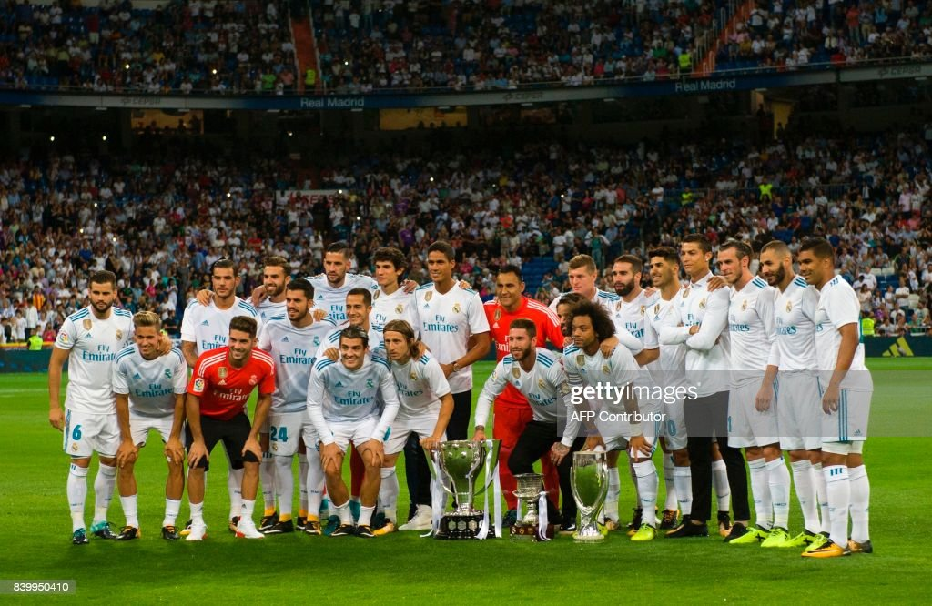Real Madrid's players pose with the Spanish Supercup (C), the Europe Super cup (R), and the Spanish League cup before the Spanish league football match Real Madrid CF vs Valencia CF at the Santiago Bernabeu stadium in Madrid on August 27, 2017. /