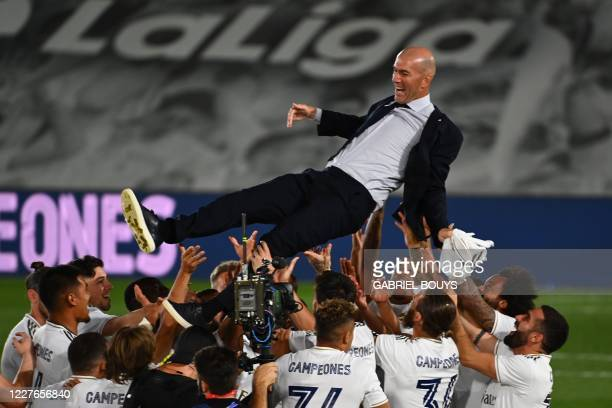 Real Madrid's players toss Real Madrid's French coach Zinedine Zidane after winning the Liga title after the Spanish League football match between...