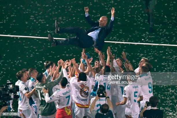TOPSHOT Real Madrid's players toss Real Madrid's French coach Zinedine Zidane at the Santiago Bernabeu stadium in Madrid on May 27 2018 during a...