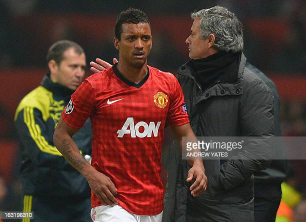 Real Madrid's Portuguese coach Jose Mourinho pats Manchester United's Portuguese midfielder Nani on the back as Nani leaves the field after being...