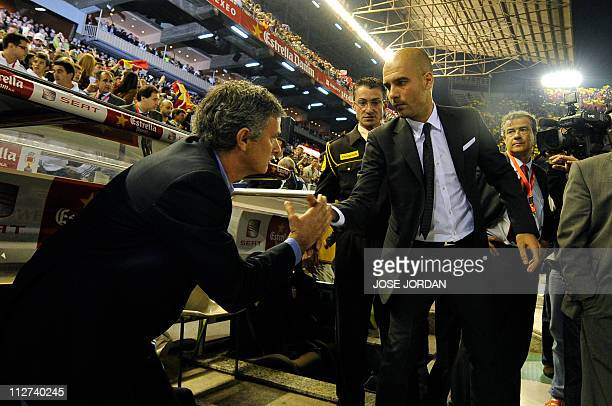 Real Madrid's Portuguese coach Jose Mourinho shakes hands with Barcelona's coach Josep Guardiola before the Spanish Cup final match Real Madrid...