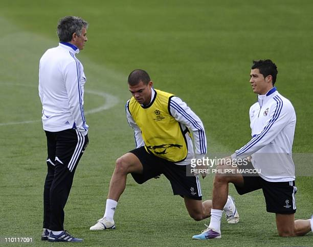 Real Madrid's Portuguese coach Jose Mourinho speaks with Portuguese defender Pepe and Portuguese forward Cristiano Ronaldo during a training session...