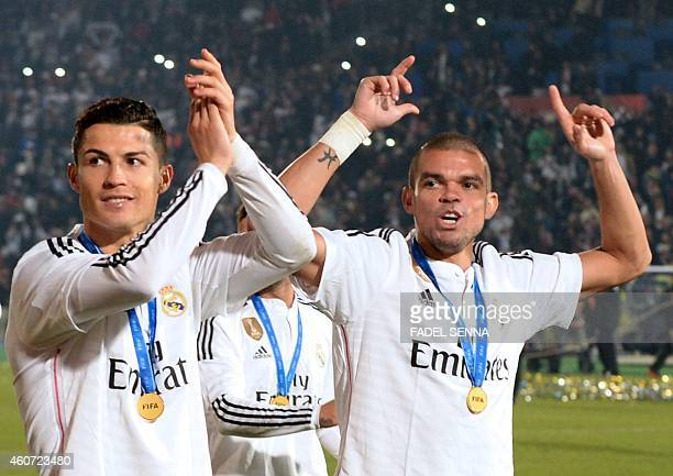 Real Madrid's Portuguese defender Pepe and Portuguese forward Cristiano Ronaldo applaud their supporters after winning the FIFA Club World Cup final...