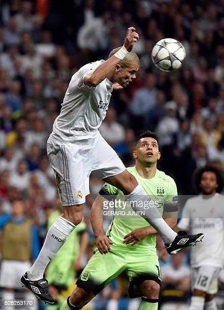 Real Madrid's Portuguese defender Pepe heads the ball past Manchester City's Argentinian forward Sergio Aguero during the UEFA Champions League...