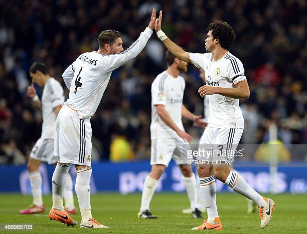 Real Madrid's Portuguese defender Pepe is congratuled by Real Madrid's defender Sergio Ramos during the Spanish Copa del Rey semifinal firstleg...