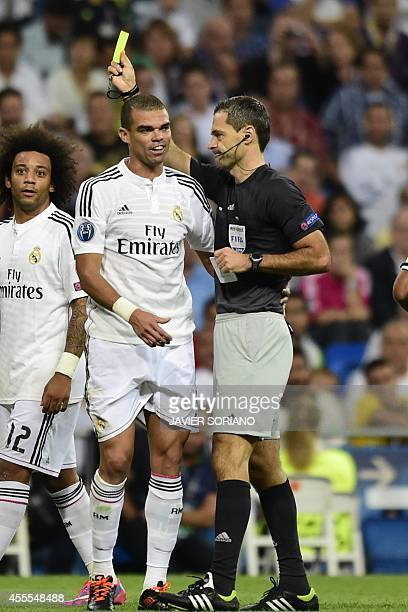 Real Madrid's Portuguese defender Pepe is shown a yellow card by referee during the UEFA Champions League football match Real Madrid CF vs FC Basel...