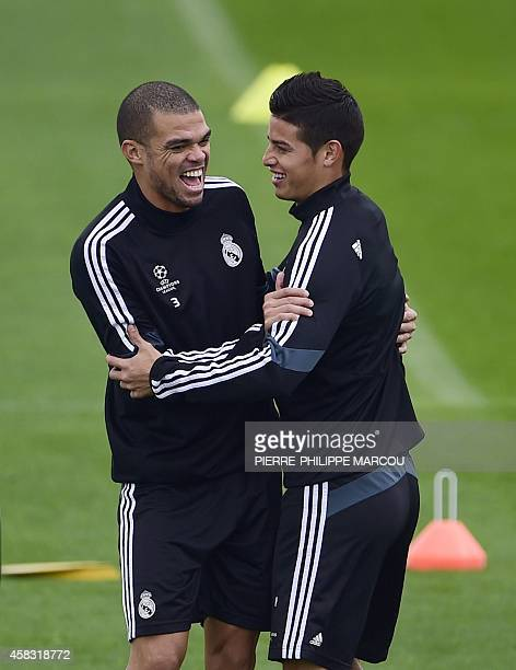 Real Madrid's Portuguese defender Pepe jokes with Real Madrid's Colombian midfielder James Rodriguez during a training session at the Valdebebas...