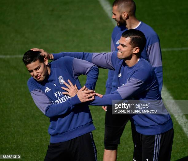 Real Madrid's Portuguese defender Pepe jokes with Real Madrid's Colombian midfielder James Rodriguez during a training session at Valdebebas Sport...