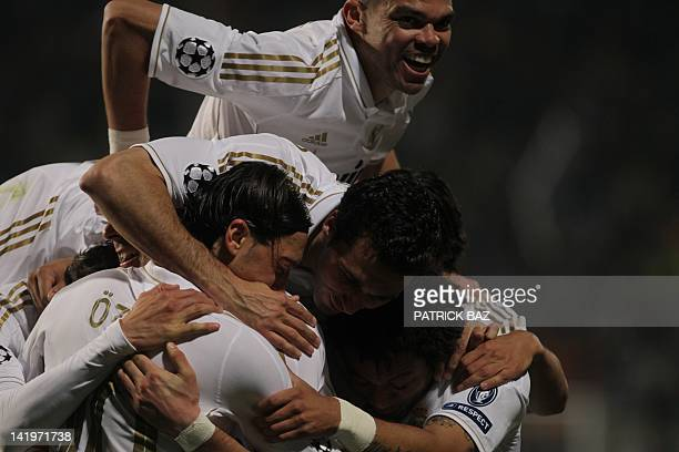 Real Madrid's Portuguese defender Pepe jumps on top of his team mates in celebration after the Spanish club scored their third goal during their UEFA...