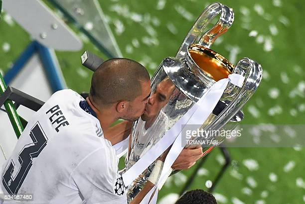 TOPSHOT Real Madrid's Portuguese defender Pepe kisses the trophy after winning the UEFA Champions League final football match against Atletico Madrid...