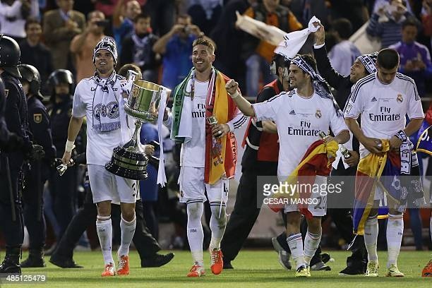 Real Madrid's Portuguese defender Pepe Real Madrid's defender Sergio Ramos and Real Madrid's midfielder Isco celebrate with the trophy after winning...