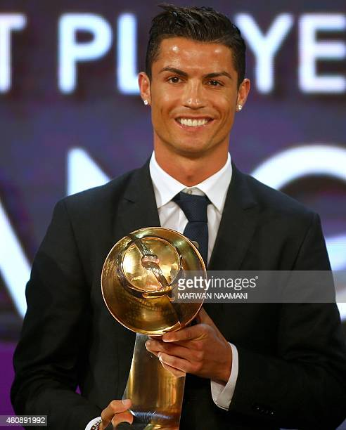 """Real Madrid's Portuguese football player Cristiano Ronaldo poses with his """"Best Player of the Year"""" award during the Globe Soccer Awards Ceremony at..."""