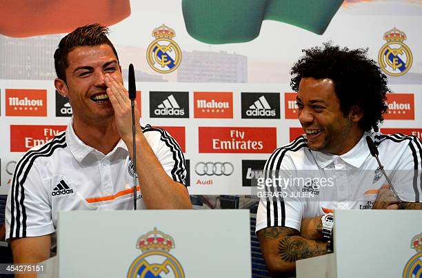 Real Madrid's Portuguese forward Cristiano Ronaldo and Brazilian defender Marcelo laugh as they give a press conference with their teammates to give...