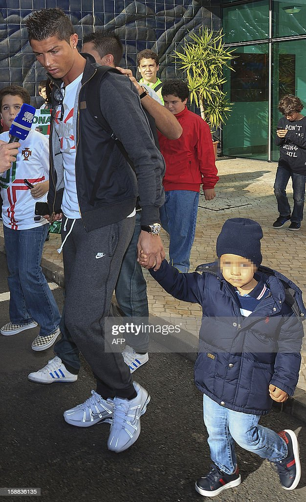 Real Madrid's Portuguese forward Cristiano Ronaldo (L) and his son Cristiano Jr arrive at Madeira airport in Funchal on December 31, 2012.