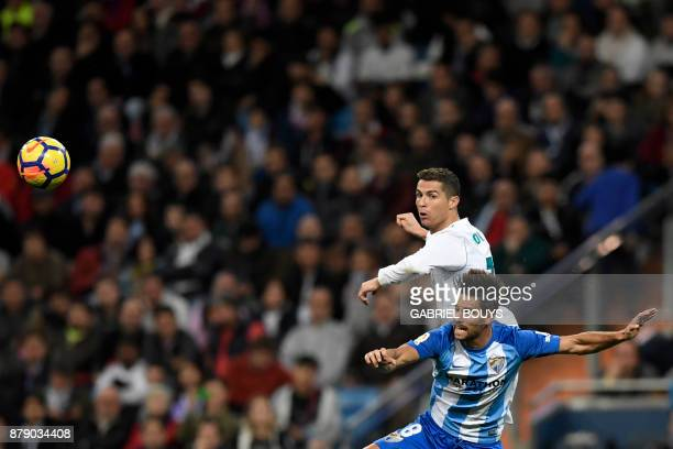 Real Madrid's Portuguese forward Cristiano Ronaldo and Malaga's Spanish midfielder Adrian Gonzalez Morales jump for the ball during the Spanish...
