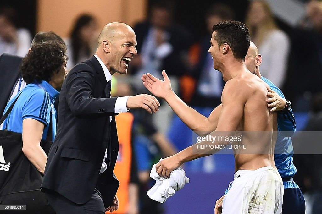 Real Madrid's Portuguese forward Cristiano Ronaldo (R) and Real Madrid's French coach Zinedine Zidane celebrate after Real Madrid won the UEFA Champions League final football match over Atletico Madrid at San Siro Stadium in Milan, on May 28, 2016. / AFP / FILIPPO