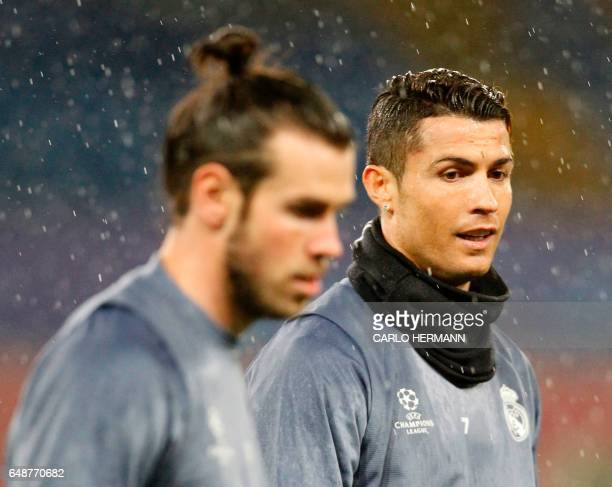 Real Madrid's Portuguese forward Cristiano Ronaldo and Real Madrid's Welsh forward Gareth Bale attend a training session under heavy rain on the eve...