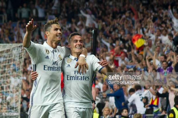 Real Madrid's Portuguese forward Cristiano Ronaldo and Real Madrid's midfielder Lucas Vazquez celebrate their 30 victory over Atletico at the end of...