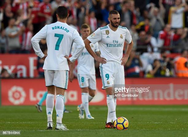 Real Madrid's Portuguese forward Cristiano Ronaldo and Real Madrid's French forward Karim Benzema stand on the field after Girona's goal during the...