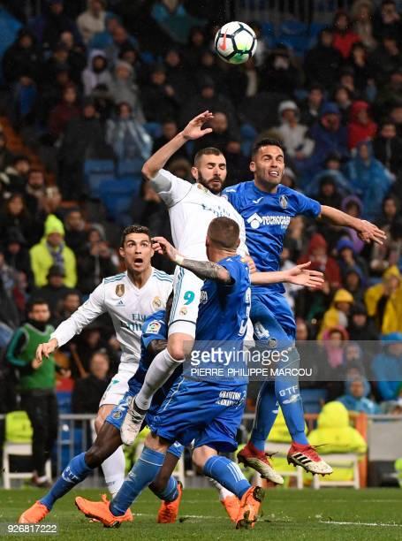 Real Madrid's Portuguese forward Cristiano Ronaldo and Real Madrid's French forward Karim Benzema vies with Getafe's Spanish defender Bruno Gonzalez...
