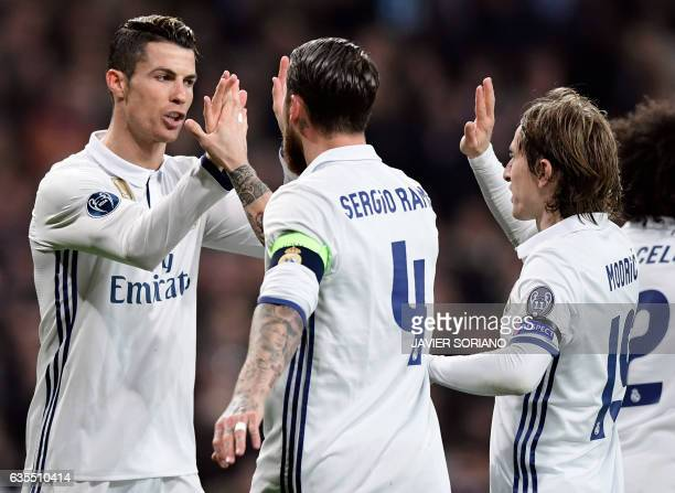 Real Madrid's Portuguese forward Cristiano Ronaldo and teammates celebrate their third goal during the UEFA Champions League round of 16 first leg...