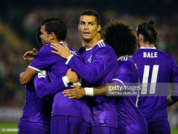 Real Madrid's Portuguese forward Cristiano Ronaldo and teammates congratulate Real Madrid's midfielder Isco after scoring during the Spanish league...