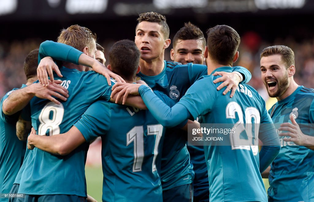 TOPSHOT - Real Madrid's Portuguese forward Cristiano Ronaldo (C) and teammates celebrate Real Madrid's German midfielder Toni Kroos' goal (2L) during the Spanish league football match between Valencia CF and Real Madrid CF at the Mestalla stadium in Valencia on January 27, 2018. /