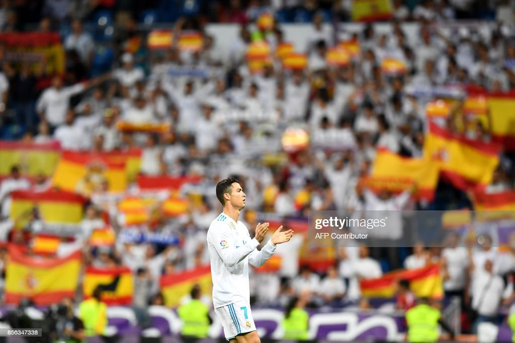 Real Madrid's Portuguese forward Cristiano Ronaldo applauds as Real Madrid's fans cheer with Spanish flags before the Spanish league football match Real Madrid CF vs RCD Espanyol at the Santiago Bernabeu stadium in Madrid on October 1, 2017. /