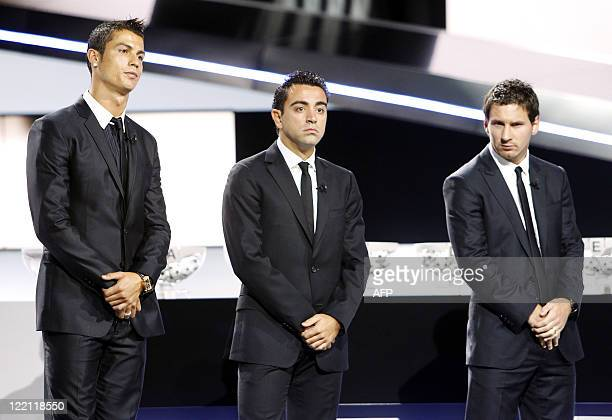 Real Madrid's Portuguese forward Cristiano Ronaldo Barcelona's Spanish midfielder Xavier Hernandez and Argentinian forward Lionel Messi wait for the...