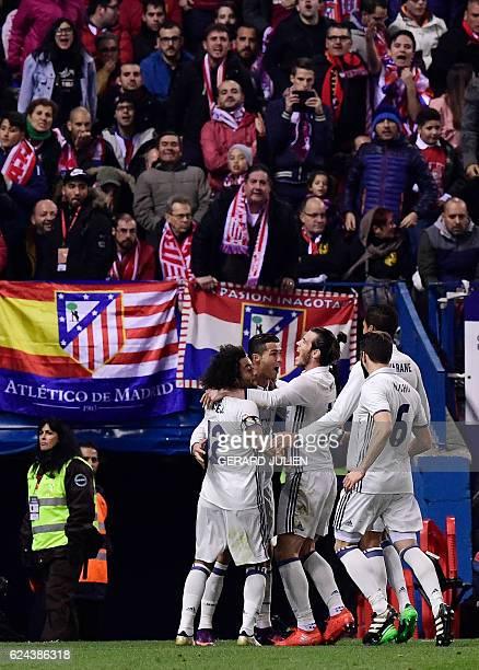 Real Madrid's Portuguese forward Cristiano Ronaldo celebrates a goal with teammates during the Spanish league football match between Club Atletico de...