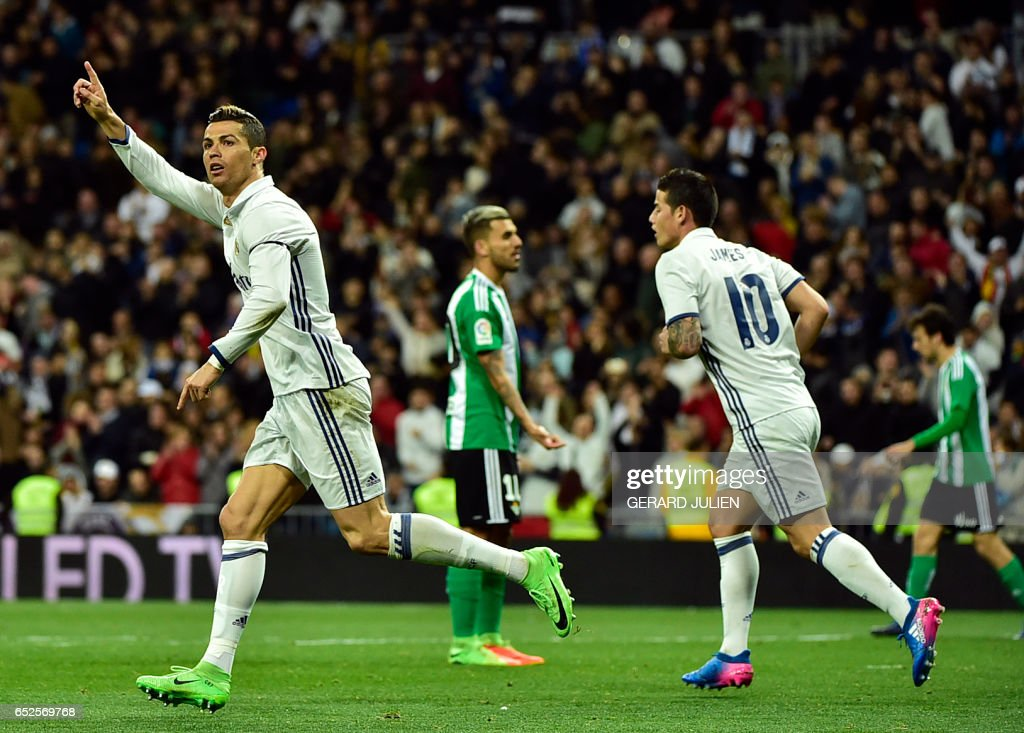 TOPSHOT - Real Madrid's Portuguese forward Cristiano Ronaldo (L) celebrates a goal beside Real Madrid's Colombian midfielder James Rodriguez during the Spanish league footbal match Real Madrid CF vs Real Betis at the Santiago Bernabeu stadium in Madrid on March 12, 2017. /