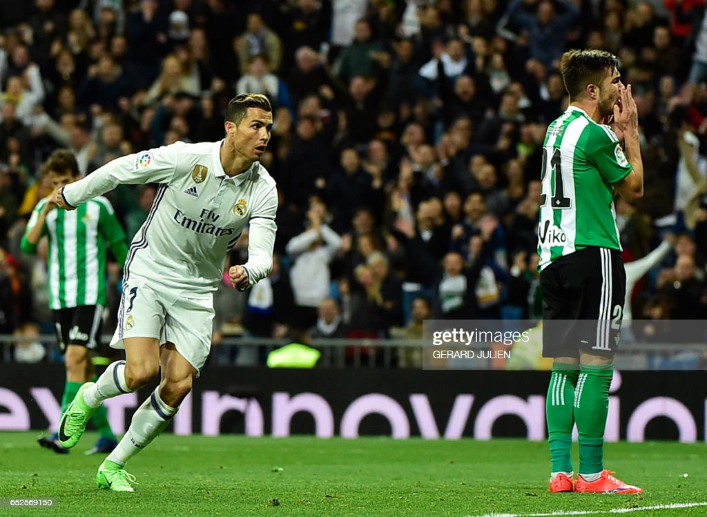 Real Madrid's Portuguese forward Cristiano Ronaldo (L) celebrates after scoring a goal beside Betis' Romanian midfielder Alin Tosca during the Spanish league footbal match Real Madrid CF vs Real Betis at the Santiago Bernabeu stadium in Madrid on March 12, 2017. /
