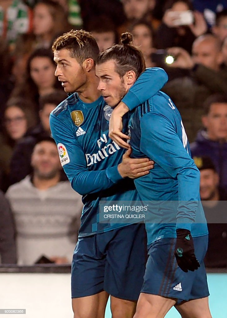 Real Madrid's Portuguese forward Cristiano Ronaldo (L) celebrates after scoring a goal with Real Madrid's Welsh forward Gareth Bale during the Spanish Liga football match Real Betis vs Real Madrid at the Benito Villamarin stadium in Sevilla on February 18, 2018. / AFP PHOTO / Cristina Quicler