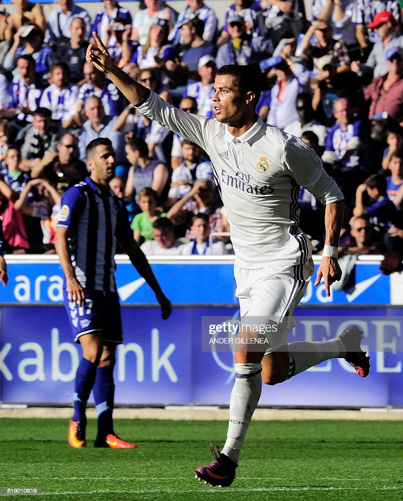 Real Madrid's Portuguese forward Cristiano Ronaldo (R) celebrates after scoring his team's second goal during the Spanish league football match between Deportivo Alaves and Real Madrid CF at the Mendizorroza stadium in Vitoria on October 29, 2016. / AFP / ANDER