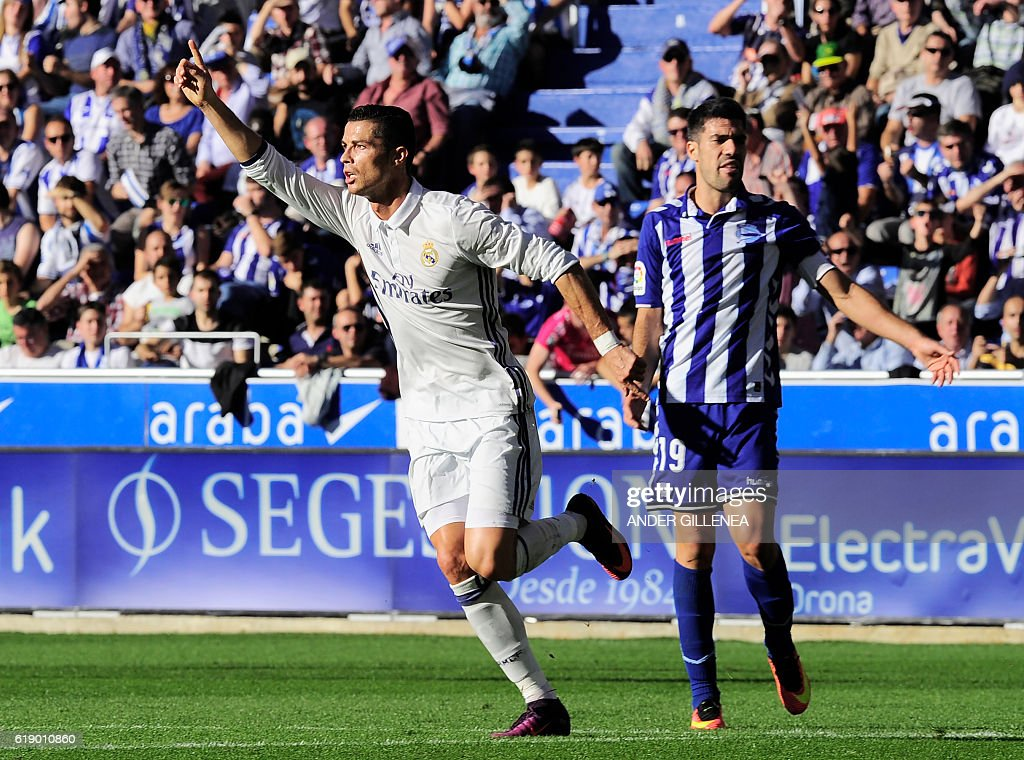 Real Madrid's Portuguese forward Cristiano Ronaldo (L) celebrates after scoring his team's second goal during the Spanish league football match between Deportivo Alaves and Real Madrid CF at the Mendizorroza stadium in Vitoria on October 29, 2016. / AFP / ANDER