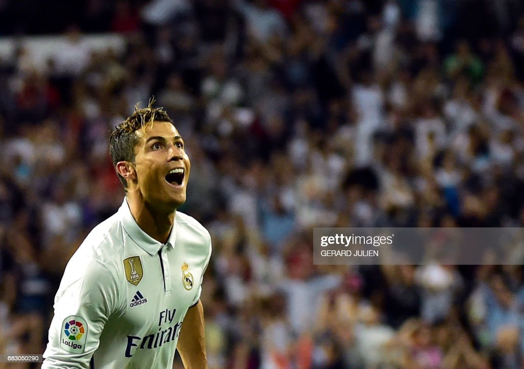 Real Madrid's Portuguese forward Cristiano Ronaldo celebrates after scoring during the Spanish league football match Real Madrid CF vs Sevilla FC at the Santiago Bernabeu stadium in Madrid on May 14, 2017. /