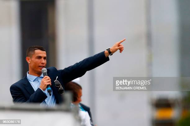 Real Madrid's Portuguese forward Cristiano Ronaldo celebrates at Cibeles square in Madrid on May 27 2018 after Real Madrid won their third Champions...