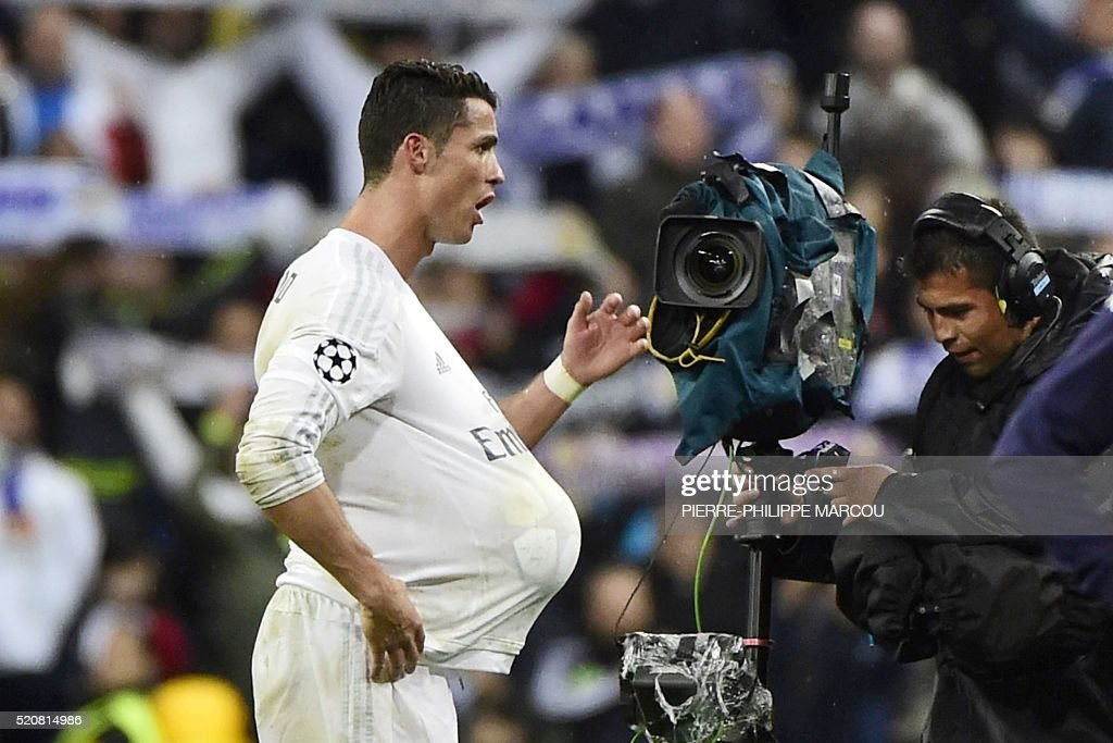 TOPSHOT - Real Madrid's Portuguese forward Cristiano Ronaldo (L) celebrates his hat trick with the ball under his shirt during the Champions League quarter-final second leg football match Real Madrid vs Wolfsburg at the Santiago Bernabeu stadium in Madrid on April 12, 2016. / AFP / PIERRE