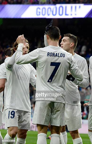 Real Madrid's Portuguese forward Cristiano Ronaldo celebrates his second goal with teammates Real Madrid's Croatian midfielder Luka Modric and Real...