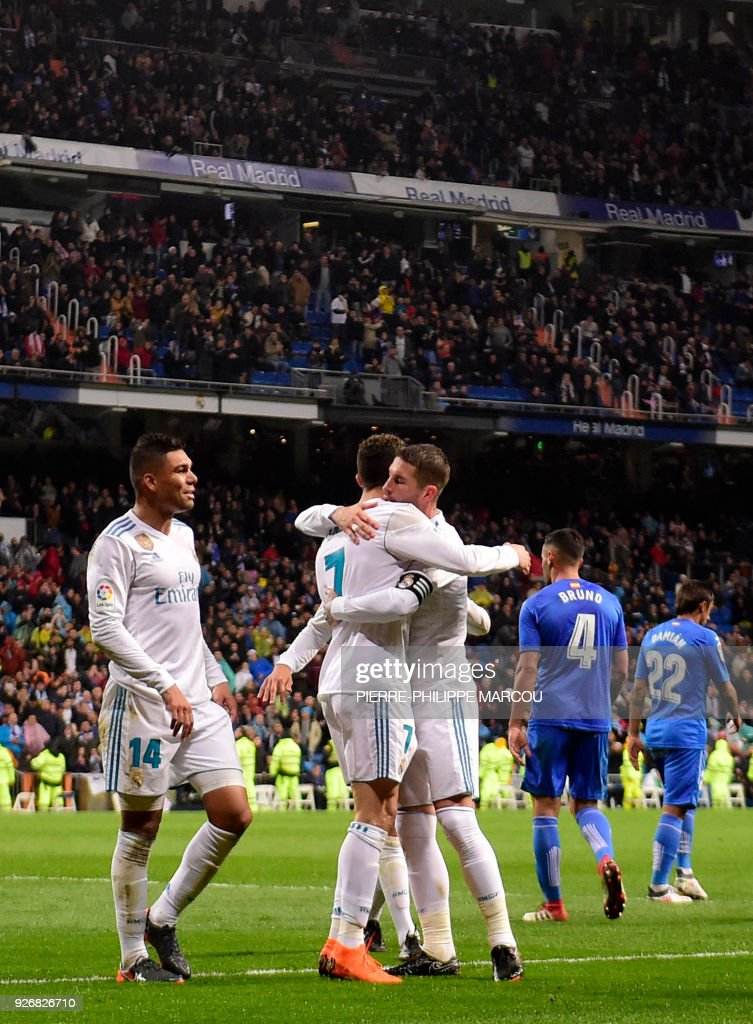 Real Madrid's Portuguese forward Cristiano Ronaldo (C) celebrates his second goal with teammates during the Spanish league football match Real Madrid CF against Getafe CF at the Santiago Bernabeu stadium in Madrid on March 3, 2018. /