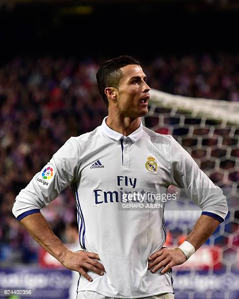 Real Madrid's Portuguese forward Cristiano Ronaldo celebrates in front of Atletico's supporters after scoring his third goal during the Spanish...